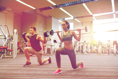 lunge: sport, bodybuilding, lifestyle and people concept - young man and woman with barbell flexing muscles and making shoulder press lunge in gym
