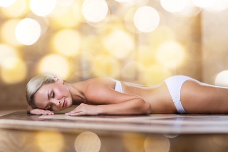 turkish bath: people, beauty, spa, bodycare and relaxation concept - beautiful young woman lying on hammam table in turkish bath over holidays lights background