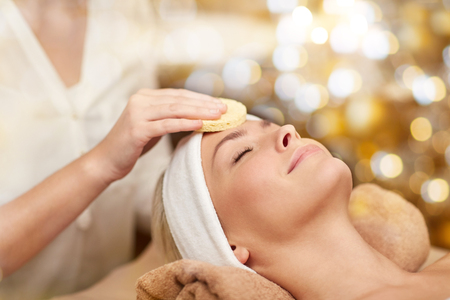 people, beauty, spa, cosmetology and relaxation concept - close up of beautiful young woman lying with closed eyes having face cleaning by sponge in spa Stock Photo