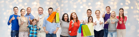 happy shopping: sale, family, generation and people concept - group of happy men and women with shopping bags and credit card showing thumbs up over holidays lights background