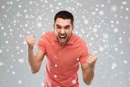 loco: emoción, gesto, invierno, Navidad y concepto de la gente - hombre joven enojado que sostiene los puños sobre la nieve sobre fondo gris Foto de archivo