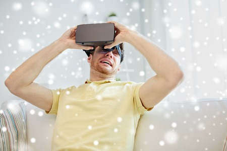 mediated: technology, augmented reality, gaming, entertainment and people concept - scared young man taking off virtual headset or 3d glasses while playing game over snow