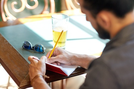people, inspiration, freelance and leisure concept - close up of man with beer writing to notebook at bar or pub