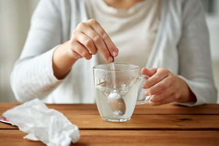 healthcare, medicine and people concept - close up of woman stirring medication in cup with spoon and paper tissue on wooden table Stock Photo