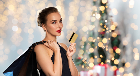 shopping card: christmas, holidays, people, luxury and sale concept - beautiful woman with credit card and shopping bags over lights background