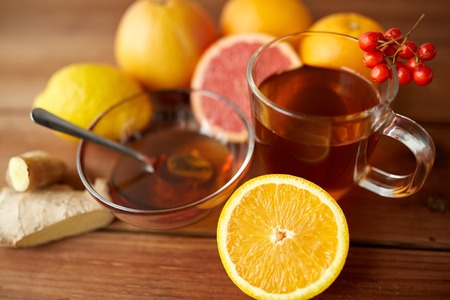 indigenous medicine: health, traditional medicine, folk remedy and ethnoscience concept - cup of ginger tea with honey, orange and rowanberry on wood