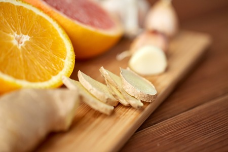 indigenous medicine: traditional medicine, cooking and ethnoscience concept - ginger, orange, grapefruit and garlic on wooden board Stock Photo