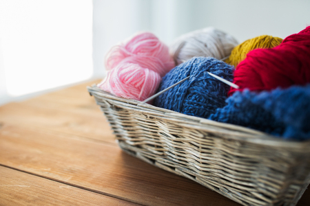 acrylic yarn: handicraft and needlework concept - wicker basket with knitting needles and balls of yarn Stock Photo