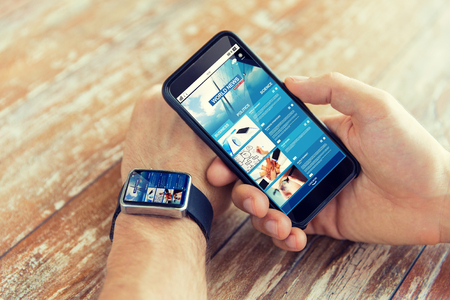 business, technology, media and people concept - close up of male hand holding smart phone and wearing watch with news web page