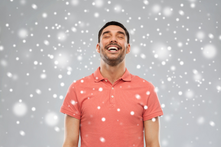 laughable: emotion, winter, christmas and people concept - laughing man over snow on gray background