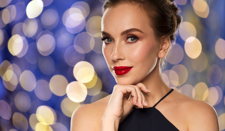 femme fatale: people, luxury and fashion concept - beautiful woman in black with red lips over blue holidays lights background