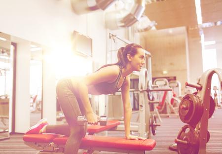 concept de remise en forme, sport, formation et personnes - femme souriante avec haltères flexion des muscles sur banc dans la salle de gym