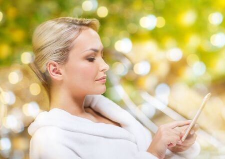 bath robe: people, beauty, lifestyle, technology and relaxation concept - beautiful young woman in white bath robe with smartphone social networking at spa over holidays lights background