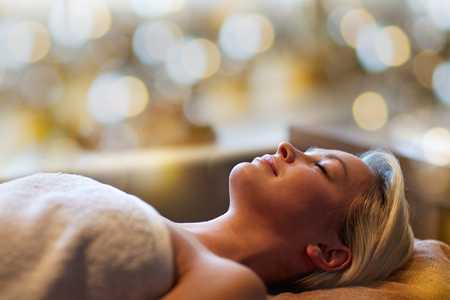 people, beauty, spa, healthy lifestyle and relaxation concept - beautiful young woman lying with closed eyes in spa Stock Photo