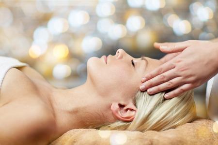 ludzie, uroda, spa, zdrowy styl życia i koncepcja relaksu - zbliżenie pięknej młodej kobiety leżącej z zamkniętymi oczami i wykonującej masaż twarzy lub głowy w spa Zdjęcie Seryjne