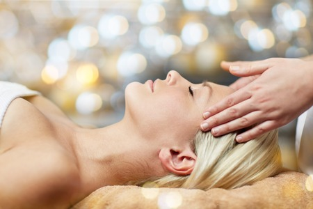 people, beauty, spa, healthy lifestyle and relaxation concept - close up of beautiful young woman lying with closed eyes and having face or head massage in spa Imagens
