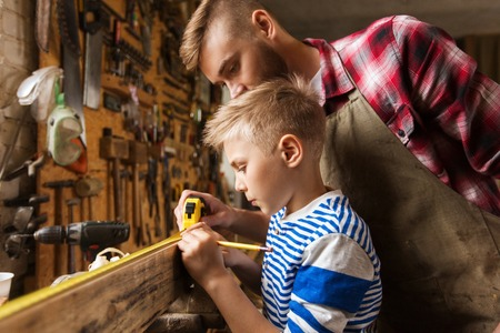 woodworker: family, carpentry, woodwork and people concept - father and little son with ruler and pencil measuring wood plank at workshop Stock Photo