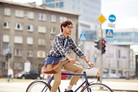 shoulder bag: people, style, leisure and lifestyle - young hipster man with shoulder bag and earphones riding fixed gear bike on city street