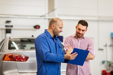 auto service, repair, maintenance and people concept - mechanic with clipboard talking to man or owner at car shop