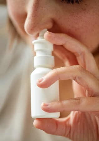 healthcare, flu, rhinitis, medicine and people concept - close up of sick woman using nasal spray Stock Photo