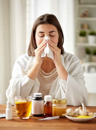 rheum: health care, flu, hygiene, age and people concept - sick woman with medicine blowing nose to paper wipe at home