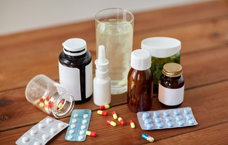 healthcare, medicine and drugs concept - pills, nasal spray, antipyretic syrup and glass on wooden table
