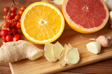 traditional medicine, cooking, food and ethnoscience concept - orange, grapefruit with ginger and garlic on wooden board
