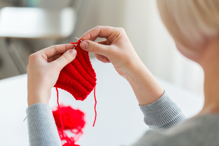people and needlework concept - woman hands knitting with needles and red yarn