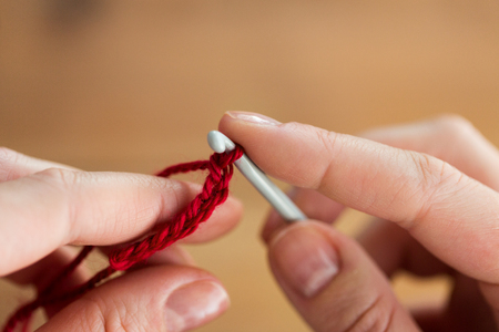people and needlework concept - close up of hands knitting with crochet hook and red yarn