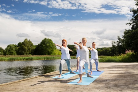 sport fitness: fitness, sport, and healthy lifestyle concept - group of people making yoga in warrior pose on river or lake berth Stock Photo