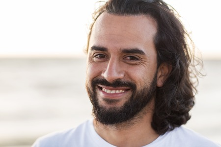 emotie, expressie en mensen concept - gelukkig lachende man met baard buitenshuis