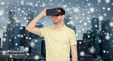 mediated: technology, augmented reality, winter, christmas and people concept - happy young man with virtual headset or 3d glasses over singapore city skyscrapers background and snow