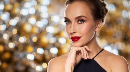 red lips: la gente, el lujo y el concepto de vacaciones - hermosa mujer en negro con labios rojos sobre el fondo de las luces
