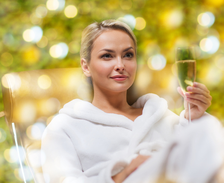 people, beauty, lifestyle, holidays and relaxation concept - beautiful young woman in white bath robe lying on chaise-longue and drinking champagne at spa over holidays lights background