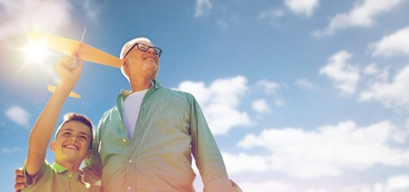 familia, generación, el futuro, el sueño y la gente concepto - feliz abuelo y nieto con avión de juguete sobre el cielo azul y las nubes de fondo