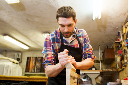 profession, carpentry, woodwork and people concept - carpenter working with plane and wood plank at workshop Stock fotó