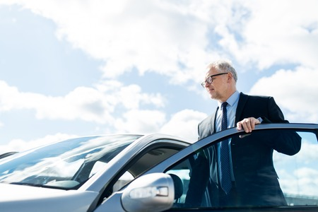 transport, business trip and people concept - senior businessman getting into car Imagens