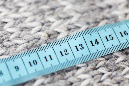 cm: handicraft, knitwear and needlework concept - close up of knitted item with measuring tape