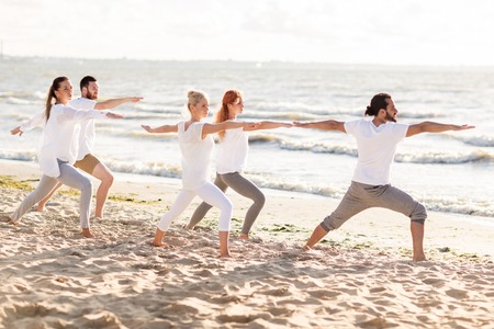 retreat: fitness, sport and healthy lifestyle concept - group of people making yoga in warrior pose on beach