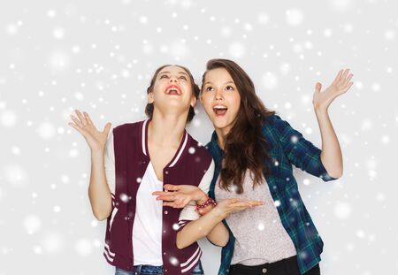 winter fashion: winter, christmas, people and holidays concept - happy smiling pretty teenage girls or friends over gray background and snow