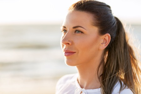 people, emotion and facial expression concept - face of happy smiling young woman on beach Stock Photo