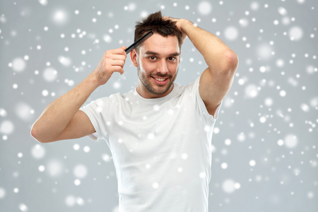 beauty, grooming, winter, christmas and people concept - smiling young man brushing hair with comb over snow on gray background Stock Photo