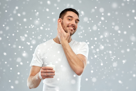 beauty, skin care, winter, christmas and people concept - smiling young man applying cream or lotion to face over snow on gray background Stock Photo