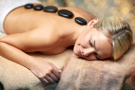 people, beauty, spa, healthy lifestyle and relaxation concept - close up of beautiful young woman having hot stone massage in spa Stock Photo