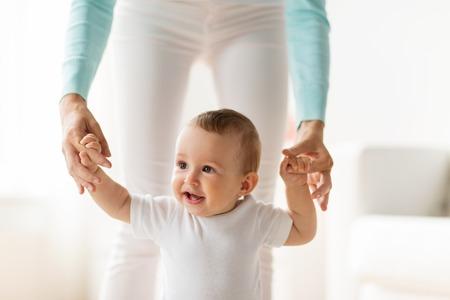 caminar: familia, niñez y el concepto de la paternidad - aprendizaje feliz pequeño bebé a caminar con la ayuda madre en el hogar