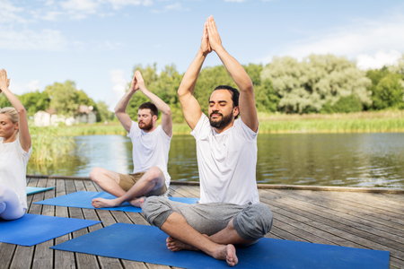 fitness, sport, yoga and healthy lifestyle concept - group of people meditating in lotus pose on river or lake berth Banco de Imagens