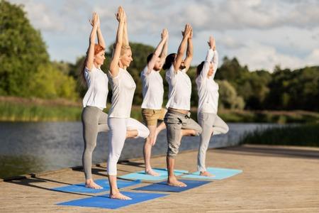 ヨガ、フィットネス、スポーツ、健康なライフ スタイル コンセプト - 人々 のグループ ツリーのポーズを取る川や湖のバースに屋外マット 写真素材 - 68094092