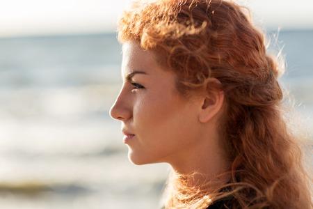 perfil de mujer rostro: personas, la expresión facial y el concepto de la emoción - la cara joven y feliz mujer pelirroja en la playa Foto de archivo