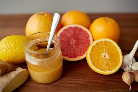 indigenous medicine: traditional medicine, cooking, food and ethnoscience concept - honey, citrus fruits with ginger and garlic on wooden table Stock Photo