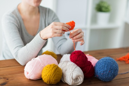 knitting, people and needlework concept - woman pulling yarn up into ball Stock Photo